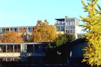 Der kleine Turm auf dem A-Block des Gymnasiums ist weithin sichtbar. Dort ist auch noch die originale Struktur zu erkennen, die für die Klassenräume jeweils einen Freiluftbereich vorsah.