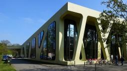 Mensa Moltke in Karlsruhe. Wenn man die wenigen Meter vom Karlsruher Schloss in Richtung Westen geht, fällt die ungewöhnliche Farbgebung als Erstes auf. Aber auch die Form des Gebäudes macht es einzigartig. Es beansprucht den urbanen Mittelpunkt im Viertel der Karlsruher Hochschulen.