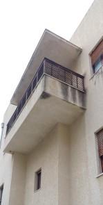Bonem-Haus in Jerusalem. Typisch sind die mit Beton-Dach versehehen Balkons. Die verstellbaren Lamellen des Geländers erlauben es, sich auf dem Balkon im Freien aufzuhalten, ohne von der Straße gesehen zu werden.