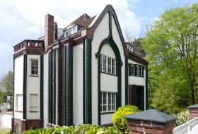 Darmstadt, Haus Behrens. Obwohl noch klar dem Jugendstil zuzuordnen, zeigt der Bau schon die Tendenzen der späteren Moderne. Das Haus wirkt allein durch seinen Form, die durch Bänder aus grün glasierten Klinkern noch verstärkt wird.