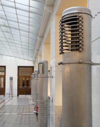Wien, Kassensaal des Postsparakssengebäudes. Wie Skulpturen aus einer anderen Welt wirken die im Kassensaal aufgestellten Lüftungsauslässe aus Aluminium. Die mannshohen Rohre scheinen mit den Besuchern sprechen zu wollen und stehen als Wächter vor den Bankschaltern.