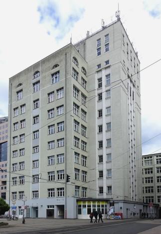 Es ist kaum zu glauben, dass die beiden Gebäude sich nur 3 Meter in der Höhe unterscheiden. Als erstes Hochhaus gilt jedoch der im rechten Bild dargestellte Bau 15 im Zeiss-Werk in Jena. Das zehn Jahre früher gebaute Darmstädter Gebäude erreicht die Höhe nur durch das steile Dach und den aufgesetzten Uhrturm.