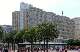 Die beiden Häuser mit dem charakteristischen weißen Glasboxen an den Stirnseiten schließen den Alexanderplatz nach Südwesten hin ab. Die Fassadenverkleidung aus hellem Kalkstein und die leicht zurückgesetzten Fenster sind typisch für die Berliner Architektur der Moderne.