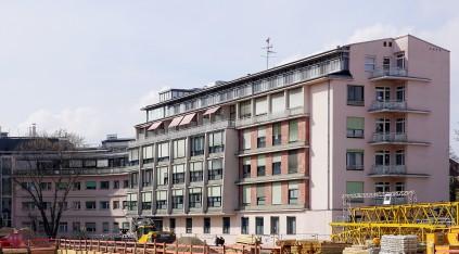 Das Hauptgebäude der Klinik und ein runder Anbau schirmen das Krankenhausgelände zur Straße hin ab. Das sechsgeschossige Gebäude wirkt durch die zurückgesetzten oberen Stockwerke mit den Balkons und die Gliederung der Fassade kleiner als es ist.