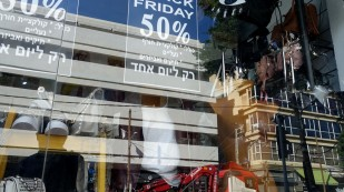 Die Struktur der weißen Balkone spiegelt sich in den Glasfassaden der Modegeschäfte am Dizengoff-Platz in Tel Aviv.