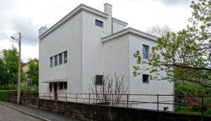 Haus Auerbach in Jena. Die Straßenseite gibt sich verschlossen. Das Grundprinzip der einfachen Form zweier ineinander geschobener Quarder wird deutlich sichtbar.