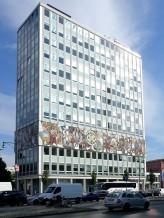 Berlin, Haus des Lehrers. Die helle Glasfassade des zwölfgeschossigen, kubischen Baukörpers des Hauses des Lehrers wird in der dritten und vierten Etage von dem umlaufenden Mosaikfries von Walter Womacka eingefasst.
