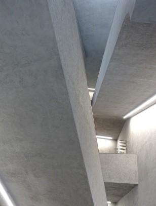 Das dominante Grau der Steine des Gebäudes setzt sich im Inneren als Rauputz und grauer Marmor fort.