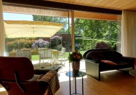 Die vom Architekten geplanten Gärten erzeugen das Gefühl, dass sich das Wohnzimmer großzügig in den Garten fortsetzt.