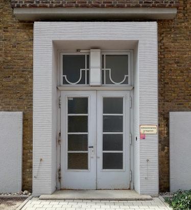Historische Verzierungen an den Eingangstüren zu den Treppenhäusern zeugen von der neunzigjährigen Geschichte des Baus.