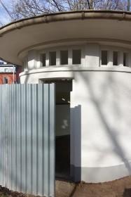 Ein runder Pavillon mit einer umlaufenden Rinne, keine Tür, keine weiteren Einbauten, nur einen separat aufgestellten Wellblech-Sichtschutz gibt es.