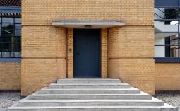 Der Haupteingang wurde unprätentiös an einen kleinen Vorbau an die Gebäudeseite verlegt, um so ein dominantes Portal zu vermeiden.