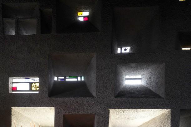 Der karg eingerichtete Innenraum wird belebt durch den Lichteinfall der unregelmäßig angebrachten, farbigen Glasfenster.