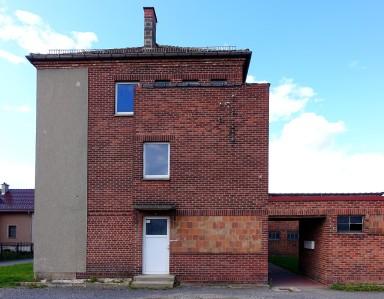 Die Stirnseite des Baus lässt noch den Übergang von der früheren Struktur zur neu angebauten Fassade erkennen.