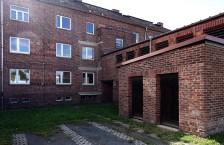 Auf der Rückseite des Baus wurden die Balkons entfernt und die Balkontüren zugemauert, um mehr Stellfläche an den Wänden der Miniküchen zu gewinnen. Die grauen Streifen der abgesägten Betonplatten sind noch sichtbar.