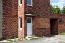 Am Seiteneingang mit der Hausnummer 7 ist noch die Struktur aus der Bauzeit zu erkennen. Deutlich sieht man die unverputzten Blocksteine, die auch zwischen den Fenstern verwendet wurden.