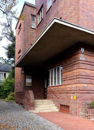 Typisch für die vom Bauhaus geprägte Architektur gibt es keinen zentrales, dominantes Eingangsportal. Der Zugang befindet sich unauffällig an der Gebäudeseite.