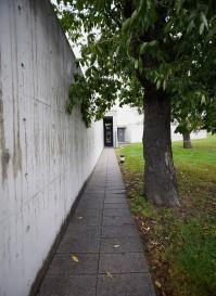 Versteckt liegt der Eingang am Ende des langen Weges zwischen Kirschbäumen und der abgewinkelten Betonmauer.