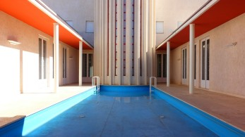 Der Atrium-Innenhof wird beherrst von einem großen Pool. Zusammen mit den vertikalen Lamellen des Treppenhausturms ergibt sich ein abstraktes Bild.