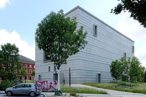 Die dick eingerahmten, unregelmäßig verteilten, kleineren Fenster haben dem Gebäude die Kritik als Bunkerbau eingebracht.